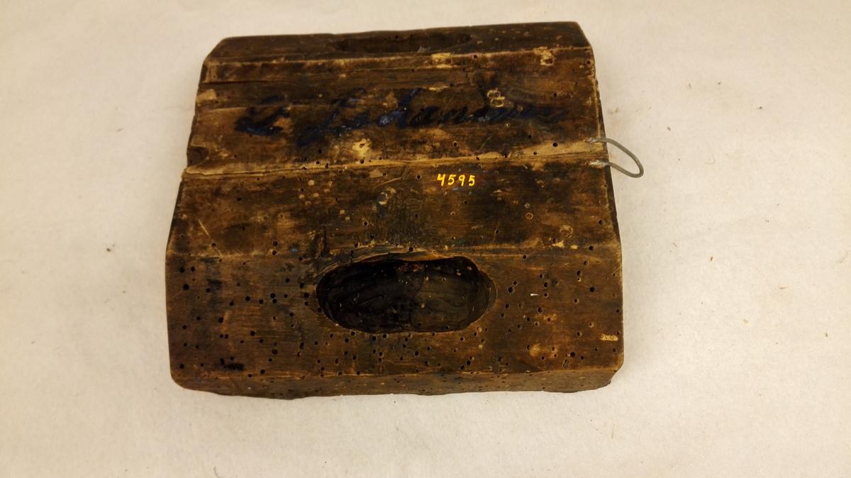 "24 tøi trykplater.  Trykplater for farvetryk og oljetryk benyttet paa et farveri i Marifjæren. Farvetrykplaterne er skaaret i træ (ek, bøk, birk og furu) medens oljetrykplaterne har figurer dannet av metal, der er paaslaaet træplater. Det tøi som blev paatrykket mønster med saadanne ""trykformer"" blev som regel benyttet kun til kvindeklær (trøie og skjørt). Undtagelsesvis til bordduker og møbeltræk. Hvor gammel denne teknik er vides ikke, men den gikk av mote for 30-50 aar siden her i Sogn.  Om trykningen meddeler farver A.E. Behaim, Marifjæren i brev av 5/8 1911 følgende: ""Tryksværten til farvetryk tilberedes paa følgede maade: Der koges kraften av 6 brissel (blaaspon), i denne avkogte kraft tilsættes to skaalpund potetsmel eller dekstrin, dette koges ind, til det er en tyk velling, saa tas det av ilden, røres uavlatelig, til det er halvvarmt, saa tilsettes et skaalpund jernbeite og denne bestaar av salpetersyre som er opløst i rustet jern... Dette røres sammen, til det er koldt.  Med denne sværte trykker man tøiet paa følgende maate: Man tar en kasse av passende høide halvfyldt med godt arbeidet leir, ovenpaa leiren lægges et skind, derpaa smøres sværten med en kost og trykplaten lægges ned paa saa sværten følger med. Det tøi som skal trykkes, lægges utover et langt bord med et underlag av tyk filt eller vadmel. Trykningen maa foregaa inde i et værelse med 20 grader varme, saa at sværten tørker efter hvert. Paa formen slaaes der med en klubbe, saa at sværten trænger sig godt ind i tøiet. Naar nu trykket er tørt rulles tøiet sammen i en rul og sættes ned i en dertil arbeidet tæt kasse med tæt laag. Saa foregaar dampingen. En kjedel paa en tøndes rum fyldes halvt med vand. Paa kjedelen maa der være et tæt laag med god pakning. Fra kjedelen gaar et rør ind i kassen hvor tøiet ligger.Man holder stærk stim oppe en time,saa dampen gaar op til 100 grader. Under dampingen gaar trykket ind i tøiet. Saa tas tøiet op av kassen, skyldes godt og tørres og presses færdigt. Denne"