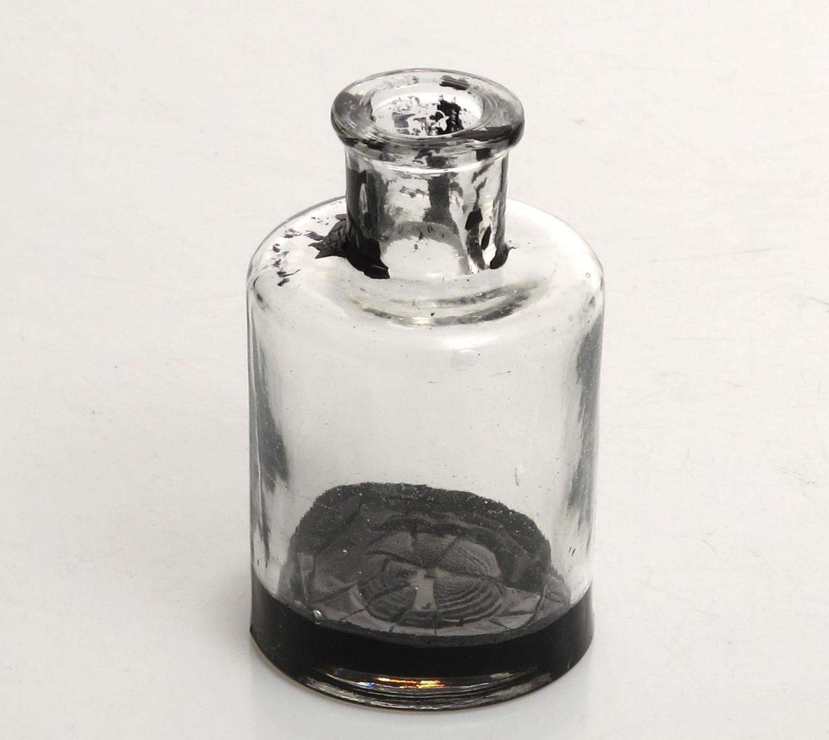 Sylindrisk flaske med fordypning i bunnen. Rette skuldre, sylindrisk hals med flat brem.