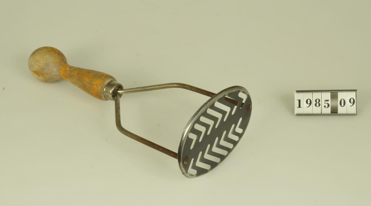 """Potatisstöt av rostfritt stål med gullackerat träskaft. Märkt: """"Rostfritt stål"""".  Upphittad på Kv. Friden, Alingsås"""