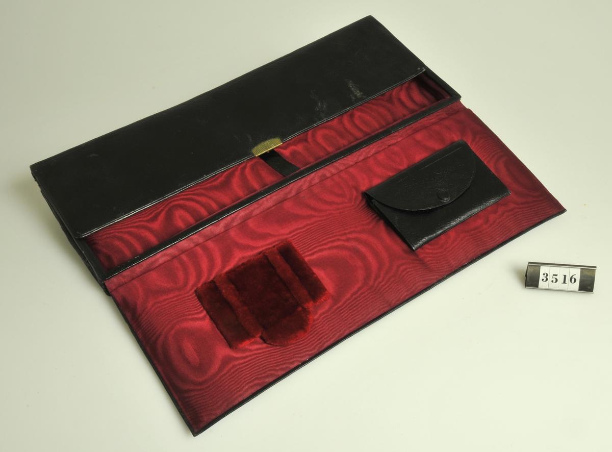 Väska tillverkad av svart läder med rött sidenfoder.