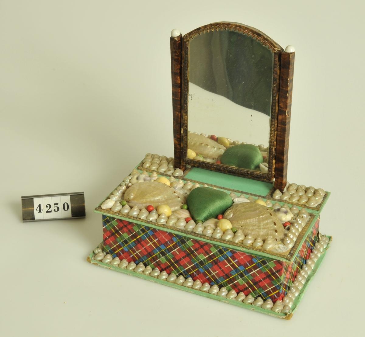 Med spegel. Låda av papp med påklistrade snäckor och en hjärtformad nåldyna av grönt siden på locket. Sidorna klädda med skotsktrutigt papper i grönt och rött. (Vanlig sjömansgåva)  Storlek: 16,5 x 10,5 cm.