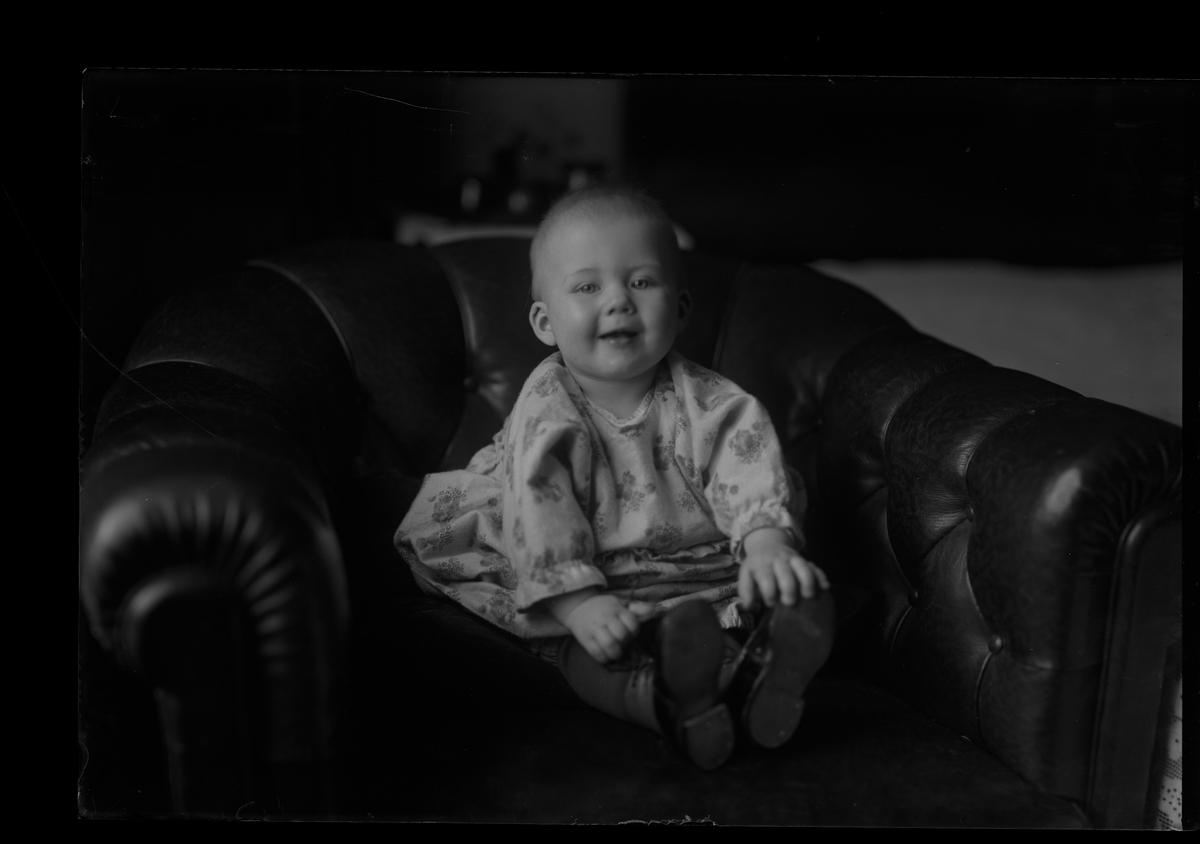 """Ett litet barn i blommig klänning och kängor sitter i en chesterfieldfåtölj. I fotografens anteckningar står det """"Nilssons barn (stadt)""""."""