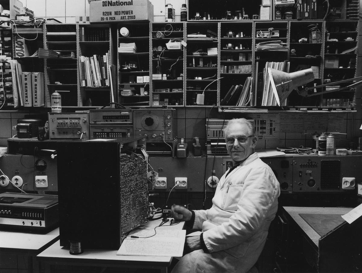 Interiörbild från reparationsverkstaden på BW-Radio-TV, som upphörde sommaren 1999. I förgrunden sitter en reparatör i vit rock och arbetar med en TV-apparat. Kvarteret Gustav 2. Stora Torget.