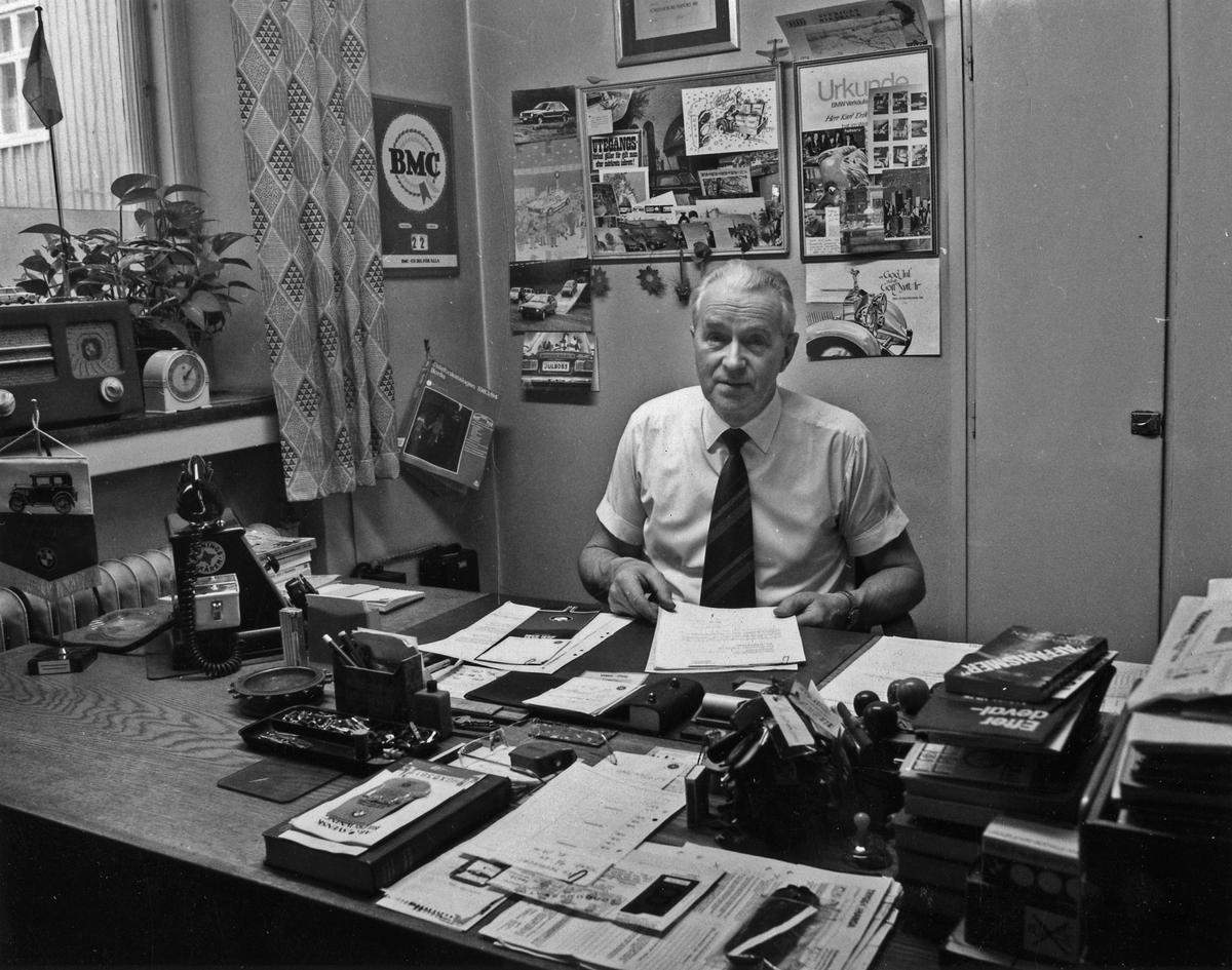 Arne Sjöberg porträtterad på sitt kontor på Ato-Motor. I vit kortärmd skjorta sitter han vid ett skrivbord och håller en bunt med papper i händerna. Kvarteret Gustaf 2. Östra Kyrkogatan 2.