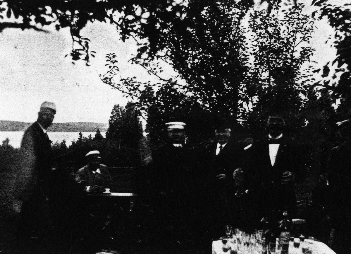 Sju män i kostym och studenmössor vid bord dukat med glas och flaskor. Bilden tagen utomhus med en sjö i bakgrunden. Alingsås herrklubb cirka 1895. På bilden syns: C.A. Ericson, J.A. Berger, Alfred Hedén, Th. Olsson, W.E. Norén, J.A. Bergmark, Gustav Nilsson