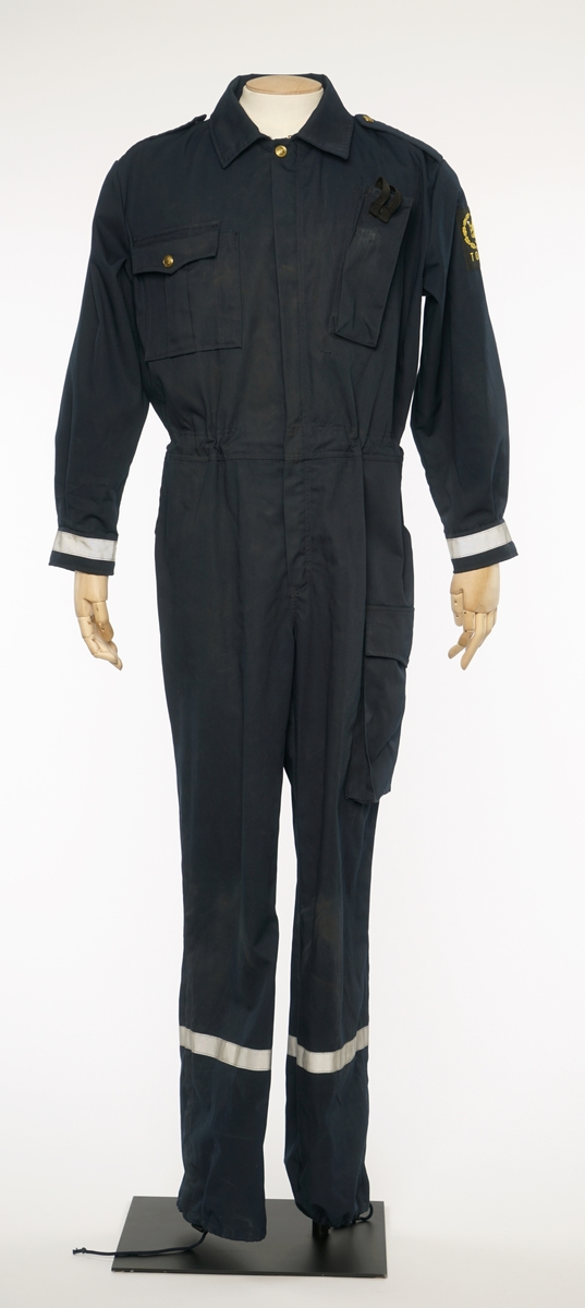 b01d2eb0 Mørkblå kjeledress med sølv refleksbånd på bukser og mansjetter. Epauletter  uten tilsatt distinksjoner. '