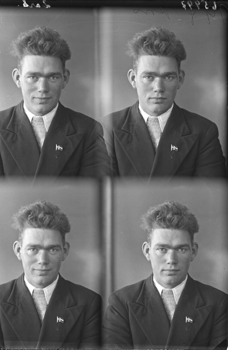 Portrett. Ung mann i mørk dress, hvit skjorte og slips. Norsk flagg på brystet. Bestilt av