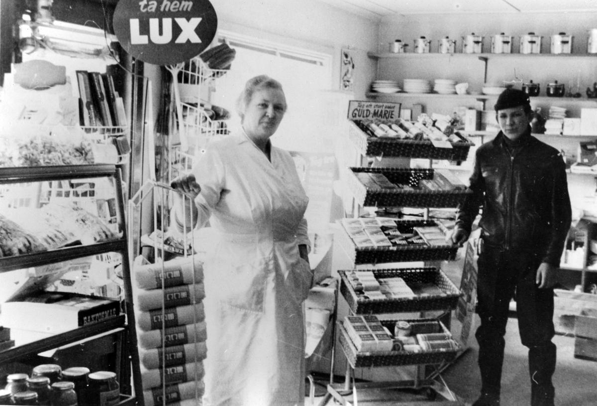 """Inifrån Kjells Speceriaffär. Till vänster en kvinna i vita arbetskläder och till höger en man. Reklamskyltar med """"Lux"""" och """"Guld Marie""""."""