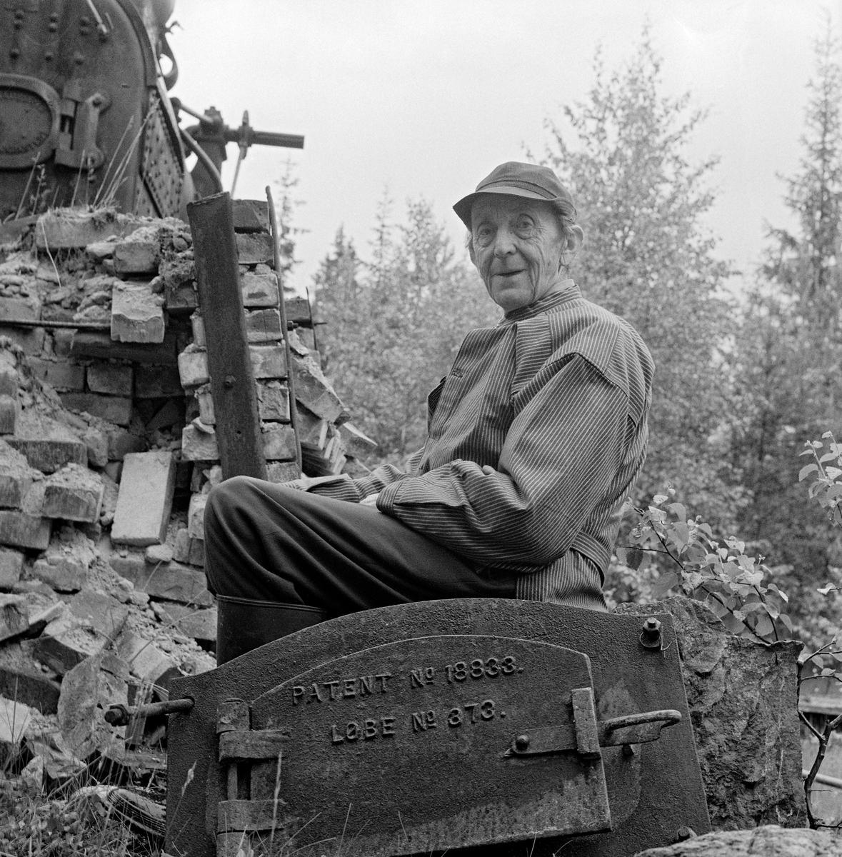 Dampmaskin, levert av O. Jakobsons maskinverksted i Kristiania, brukt på et sagbruk i Eidskog.  Her stod den ved en myrkant, delvis på et underlag av krysslagte bjelker, dels på en teglsteinsmurt oven som var bygd etter et prinsipp som var utviklet av Lauritz Sæthern (1866-1935) i Eidskog.  På dette bildet ser vi grunneier Harry Pramhus (1891-1973) posere framfor den delvis utraste ovnen med døra til fyrkjelen i forgrunnen.  Ole Jakobson var husmannssønn fra Hedmarken.  Han fikk bare folkeskoleutdanning, men som ung voksen fikk han stillingen som pedell ved Katedralskolen i hovedstaden.  Der skal han ha fått muligheter for å lære.  Det var særlig tekniske fag som interesserte Jakobson, og i 1845 startet han sitt eget verksted.  Der produserte han blant annet maskiner for landbruket, som han kjente godt fra sitt eget oppvekstmiljø.  Etter Jakobsons død ble virksomheten overtatt av sønnen, som hadde fått reise til USA for å ta den formelle utdanninga faren manglet.  Han flyttet verkstedet fra de opprinnelige lokalene i Torggata 11 til Nedre Foss, i nyere tid bedre kjent som Vulkan.  I 1894 fikk bedriften nye eiere, som flyttet virksomheten til Schultzehaugen.  Produktspekteret ble gradvis vridd fra landbruksmaskiner til vaskemaskiner (varemerket «JAKO») og klesruller.