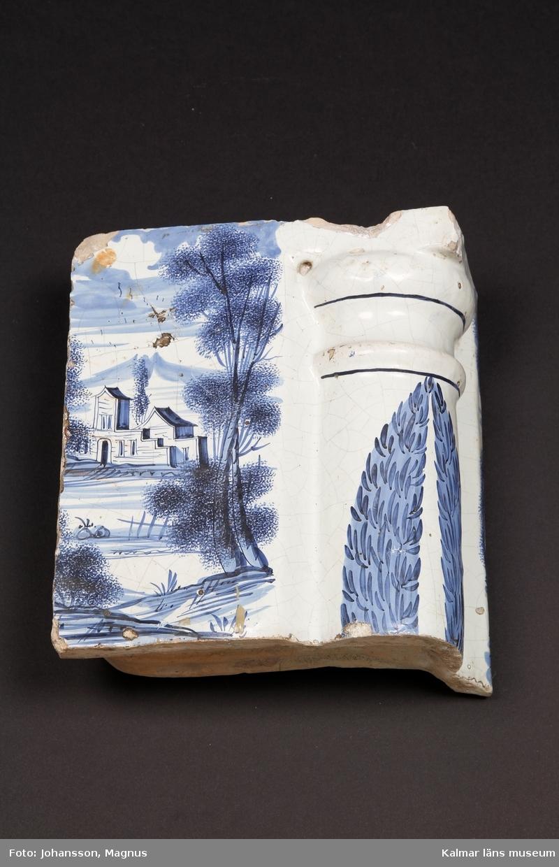 """KLM 38923. Kakel. Till flat praktkakelugn. Koboltblå dekor på vit tennglasyr och gul lergodsskärv. Drejad rump. Delftimiterande dekor med genrelandskap, figurer i 1700-tals kläder, skepp och byggnader. Simser och bårder med stiliserade blommor.   Förteckning över samtliga kakel, med mått inom parentes, gjord i samband med inventering 1997:   :1. 3 st. fasadkakel         (34,5x19x4 cm) varav 1 fragment     1 st.  -""""-    1/2 lod     (34,5x9,5x4 cm)     5 st.  -""""-                    (22x19,5x5,5 cm)     5 st.  -""""-    1/2 lod     (22x10x2,5 cm)     4 st.  -""""-                    (21,5x16-18x5,5 cm) :2. 6 st. hörnfasad         (22x21,5x10 cm) :3. 4 st. friskakel            (17,5x24x6 cm) varav 1 med sotluckshål :4. 4 st. hörnfris            (17,5x23x11 cm) :5. 2 st. friskakel            (21,5x26x6 cm) :6. 2 st. hörnfris            (21,5x21x13,5 cm) :7. 3 st. fris                   (13x26x4,5 cm) fragment :8. 1 st. hörnfris            (13x2x7 cm) fragment :9. 1 st. hörnpelare       (34,5x15x10,5 cm) :10. 2 st. krönkakel       (17x19x3,5 cm) fragment :11. 1 st. friskakel         (15x24,5x5 cm) fragment :12. 2 st. hörnfris          (15x27x12 cm) :13. 1 st. halvcirkelornament     (20x38x5 cm) :14. 9 st. simser            (4,5x12-25x4 cm)       3 st. hörnsimser     (4,5x15x11,5 cm) :15. 54 st. fragment"""