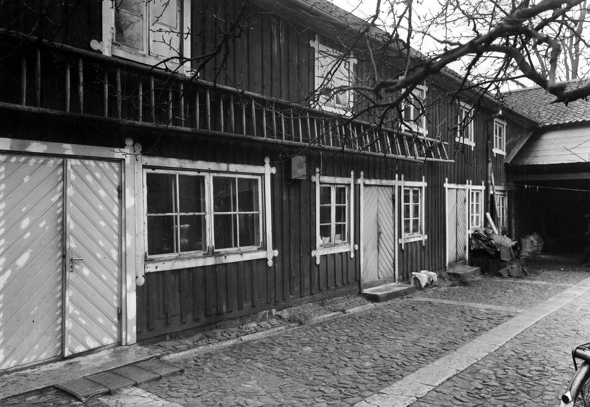 Bilden visar tvåplansbyggnaden Apoteket Hjorten (1862-1946) från gårdspartiet med 3 separata ingångar. En lång stege är fäst på väggen mellan de två våningarna och gårdsplanen utanför är kullerstensbelagd.