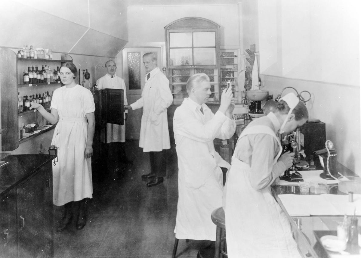 Bilden är taget inifrån Alingsås lasaretts laboratorie. 3 män och 2 kvinnor syns i rummet. På bilden syns Dr Karl Gramén, Dr Lindqvist, Dr Lindgren samt två kvinnor som saknar namnuppgift.