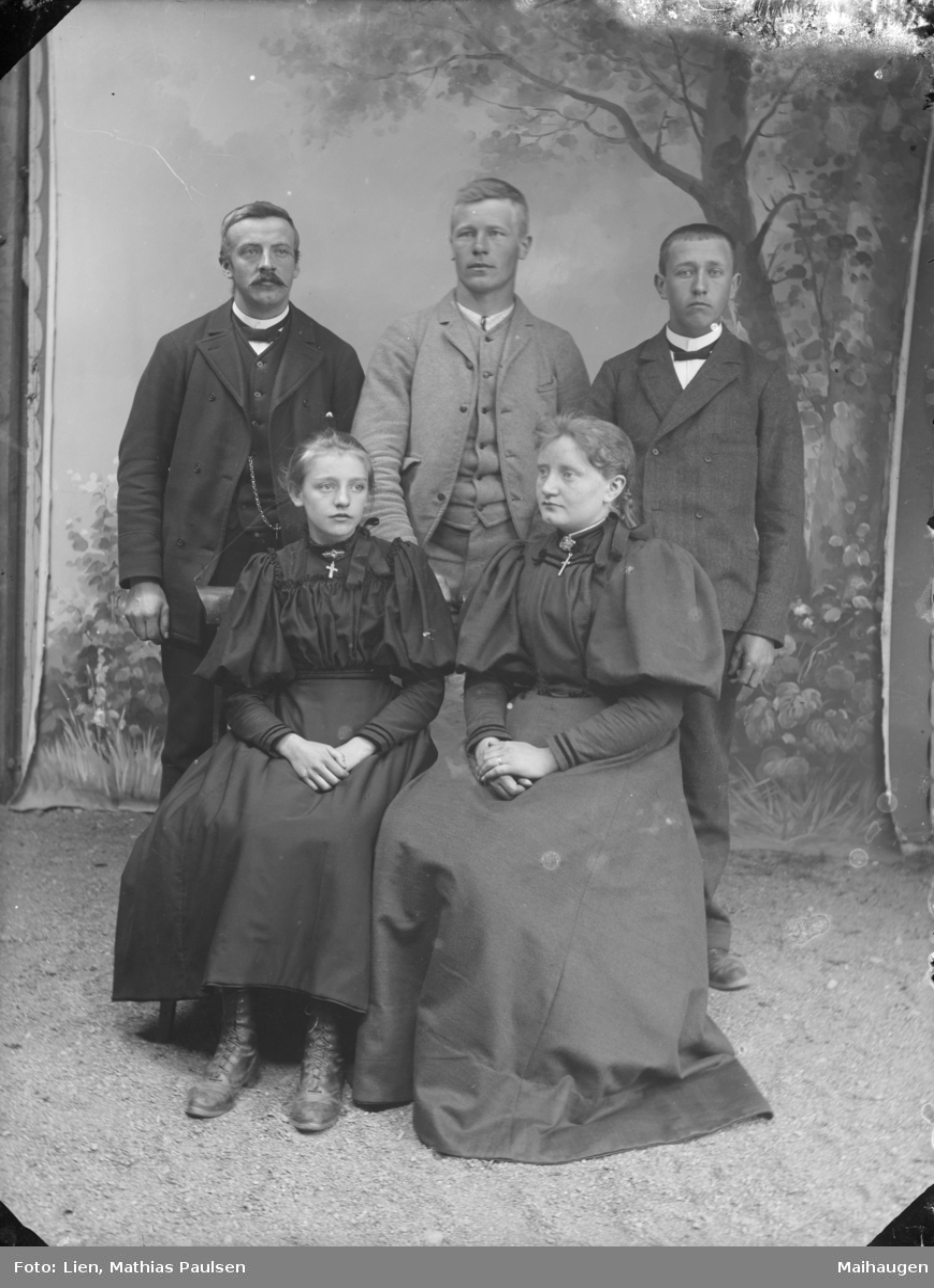 To damer og tre menn , atelierfoto med antatte familiemedlemmer.