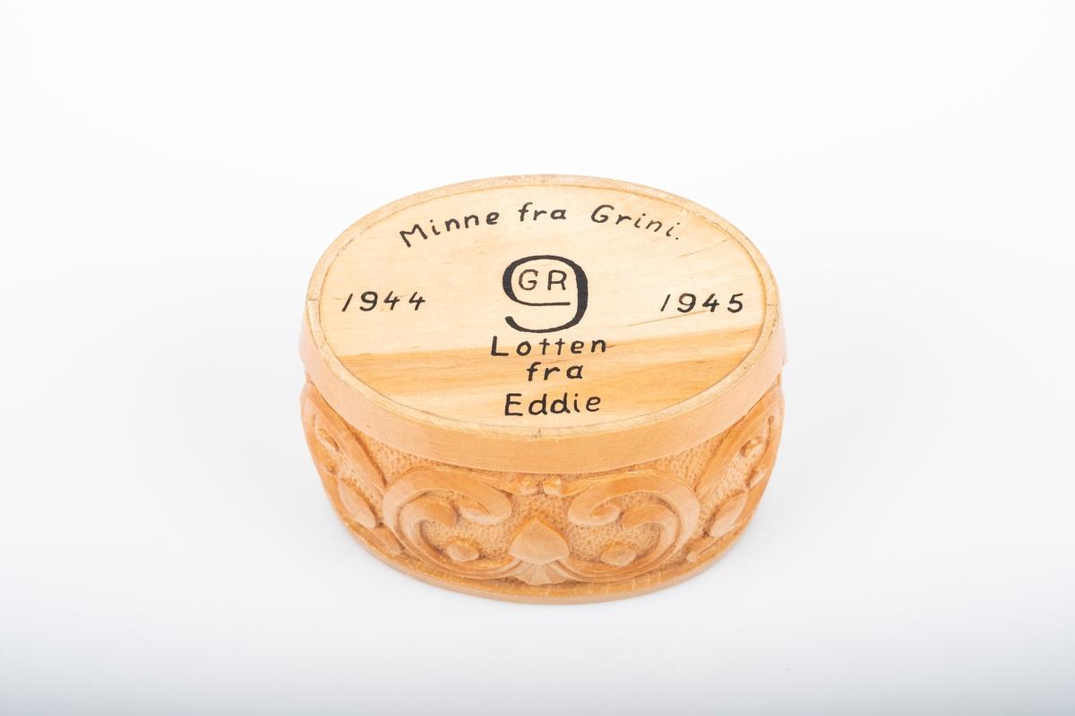 Bunn til ovalformet snusdåse i tre. Det er utskårede akantusranker rundt boksen. Det er påskrift på undersiden av bunnen.