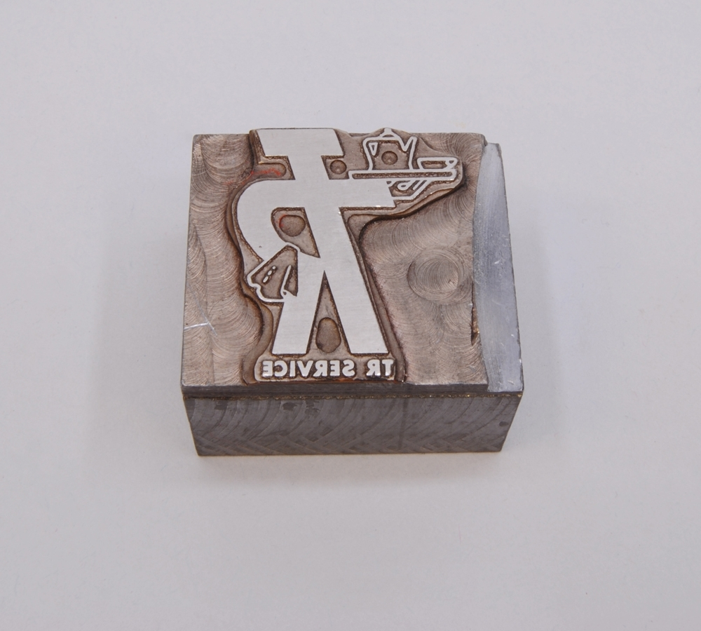 """Kliché av silverfärgad metall, monterad på en silverfärgad metallkloss. På klichén finns Trafikrestaurangers logotyp med bokstäverna """"TR"""" sammanlänkade i relief i form av """"TR-pojken"""". Logotypen kallas TR-pojken eftersom det ser ut som en person som håller armen i en serveringsgest. I ena armen håller TR-pojken en bricka med en kanna och en kopp och över den andra armen, som vilar på höften, hänger en handduk. Under logotypen finns texten: """"TR SERVICE"""" i relief."""