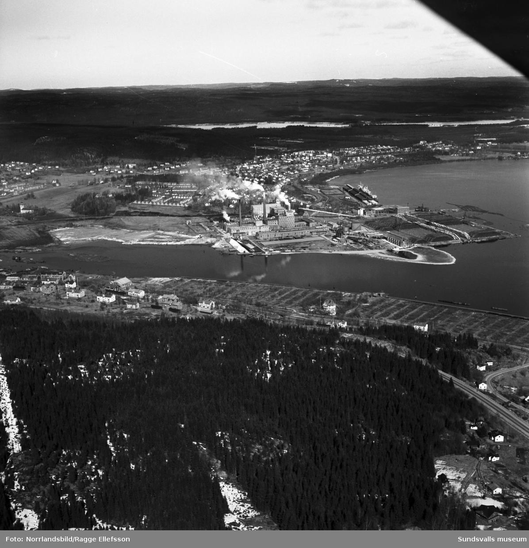Flygfoto med Östrandsfabriken i centrum. I förgrunden Skönvik, Timrå kyrka i vänsterkant och längre upp i bild Timrå tätort samt Indalsälven.