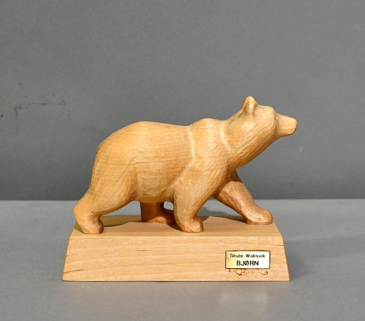 Bjørn utskåret av ett trestykke, limt på en tresokkel.