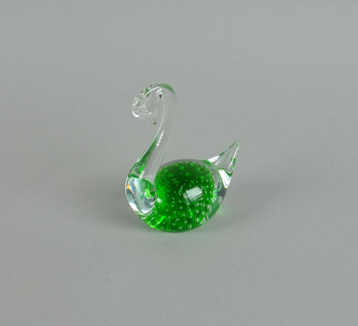 Glassfigur, forestiller svane. Glasset er grønt i midten, med dekorative bobler.