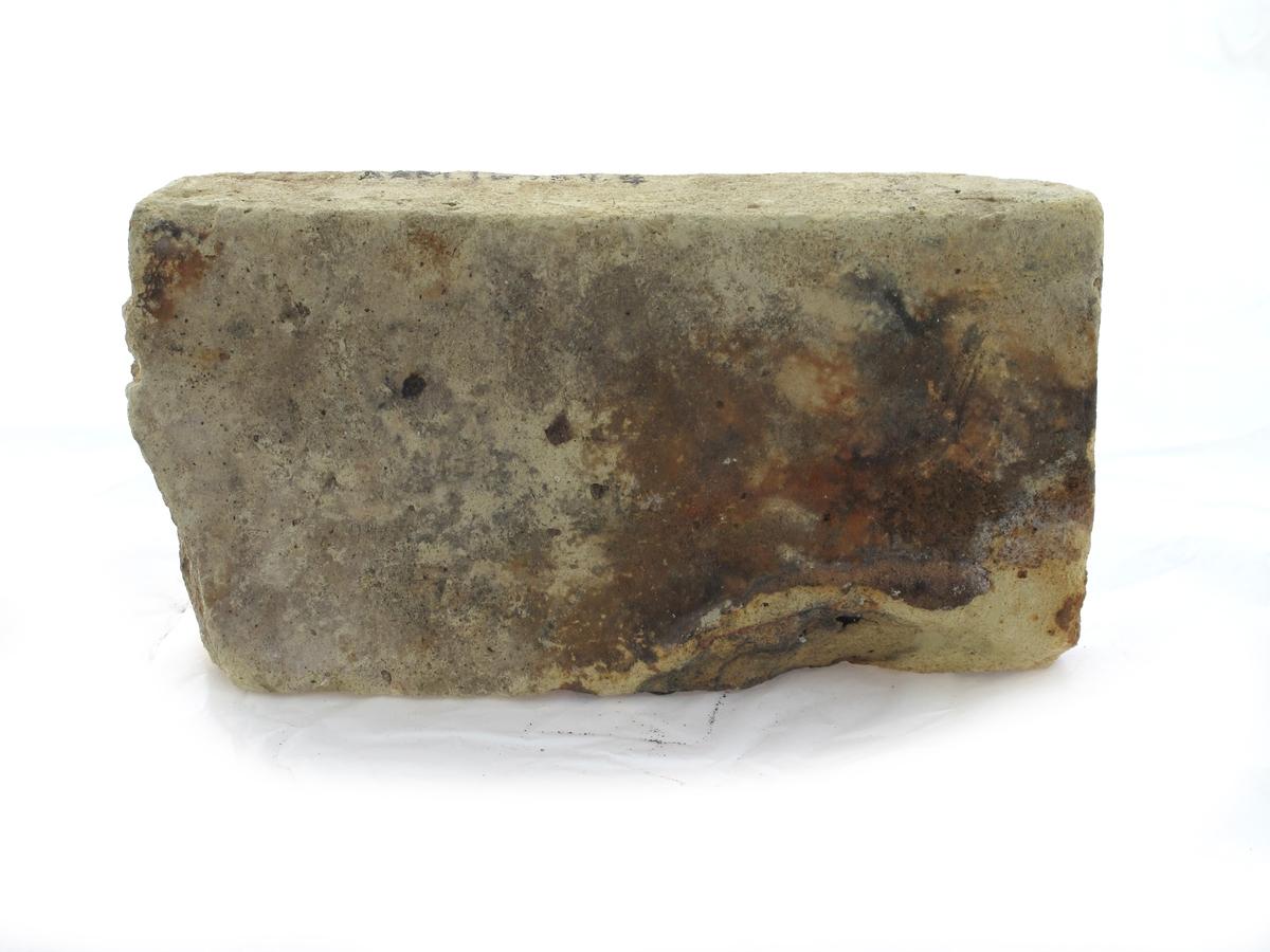 """Teglstein fra slaveskipet """"Fredensborg. Tilnærmet hel stein, litt avslått i den ene ende. Gul farge."""