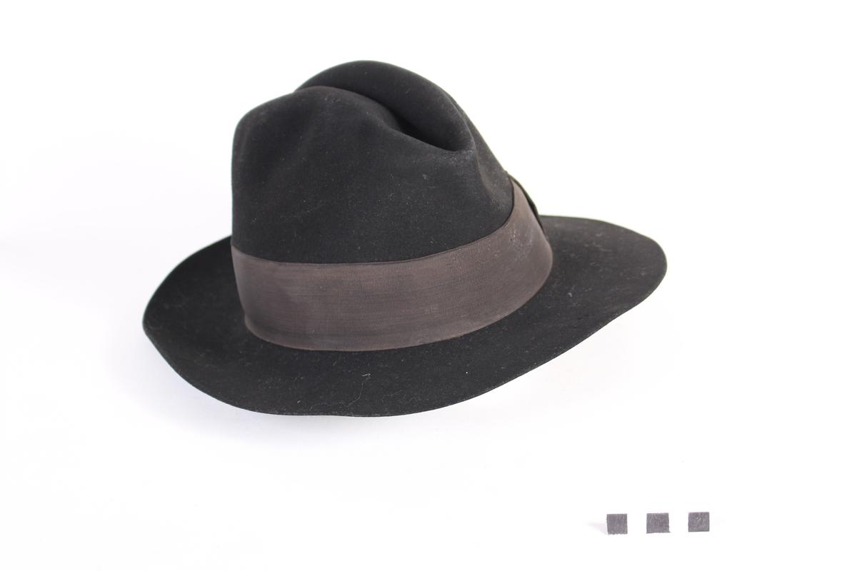 Svart hatt med bånd.