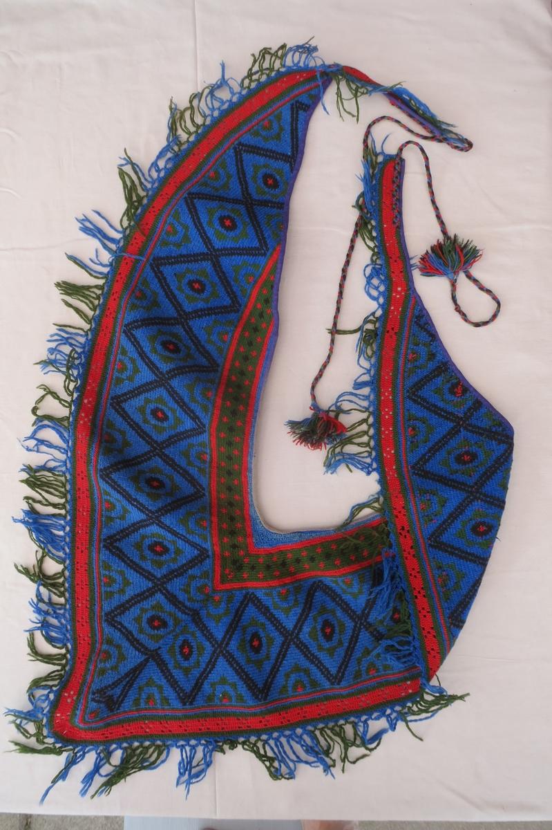 flerfärgsvirkad axelschal med förlängda framsnibbar av flätade band som läggs runt midjan och knyts bak. tofsar av garnet. Grundfärg blå, yllegarn