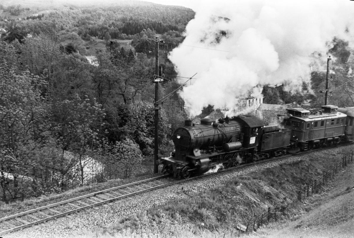 Damplokomotiv type 33a nr. 300 med persontog retning Voss, tog 618, i Midttunbakken. Elektrisk lokomotiv type El 9 nr. 2063 medfulgte toget.