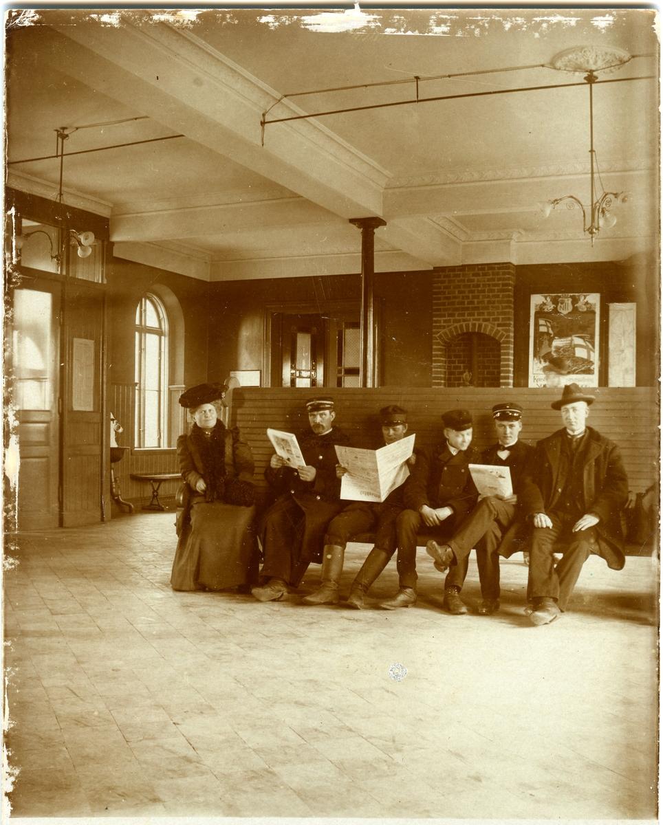 Vestibulen i Halmstads station. Uniformerad från vänster: Portvakt J.E Lindblad                                          Notisbud J.W Carlsson (bulling)