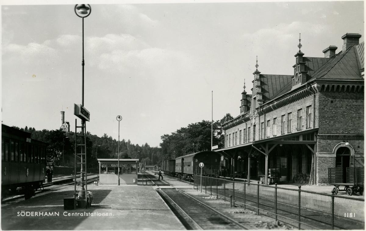 """Söderhamn station. Till vänster en Statens Järnvägar, SJ C3a och de två vagnarna till höger så kallade """"lejonburar"""" litt SJ C4. Bakom kiosken skymtar en gasvagn SJ Q4 från vilket leder en slang över spåren till C4-vagnarna. En av dessa får vid tillfället oljegas till belysningen påfyllt från Q4-vagnen. TT"""