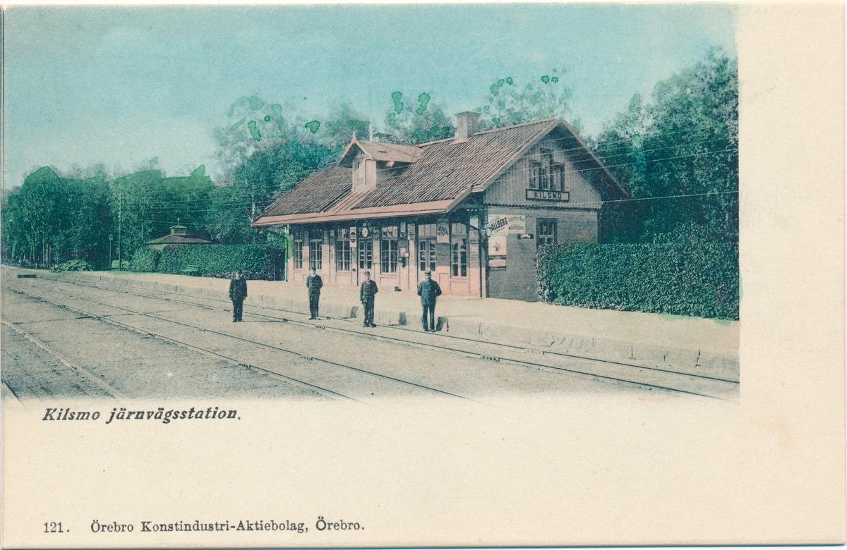 Stationspersonal framför Kilsmo järnvägsstation. Kolorerat vykort från början av 1900-talet.