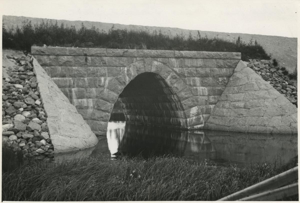 Valvbro över södraTjålmejokk. Järnvägen som går genom Jokkmokks område sträcker sig över många vattendrag, bäckar, åar och älvar. Broarna som byggdes över de anpassades till terrängen. De var framförallt funktionella men, deras utseende gick från väldigt enkla, grovhuggna till sublima, estetiskt utformade valvbroar.