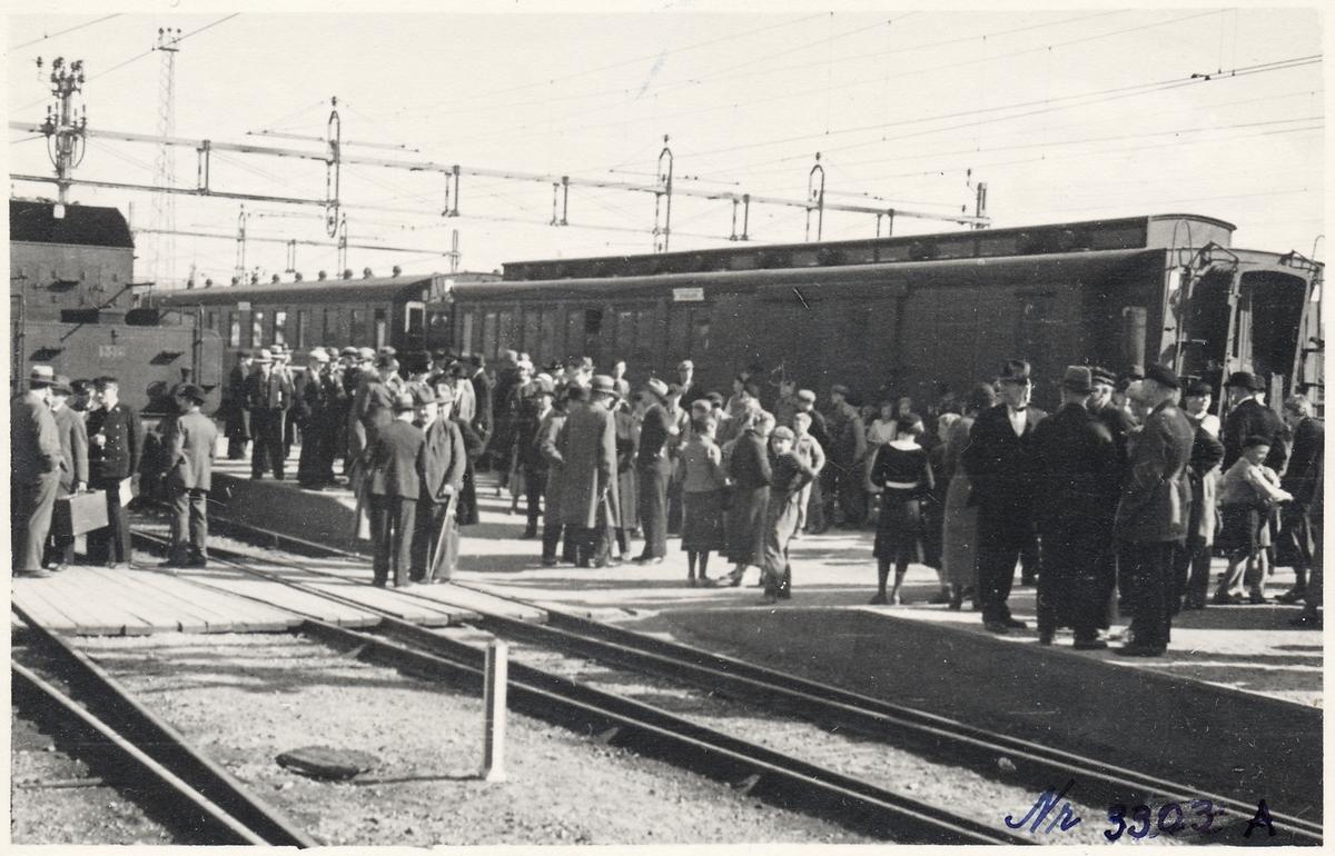 Resande på plattformen. Ånglok till vänster Statens Järnvägar SJ B 1318.