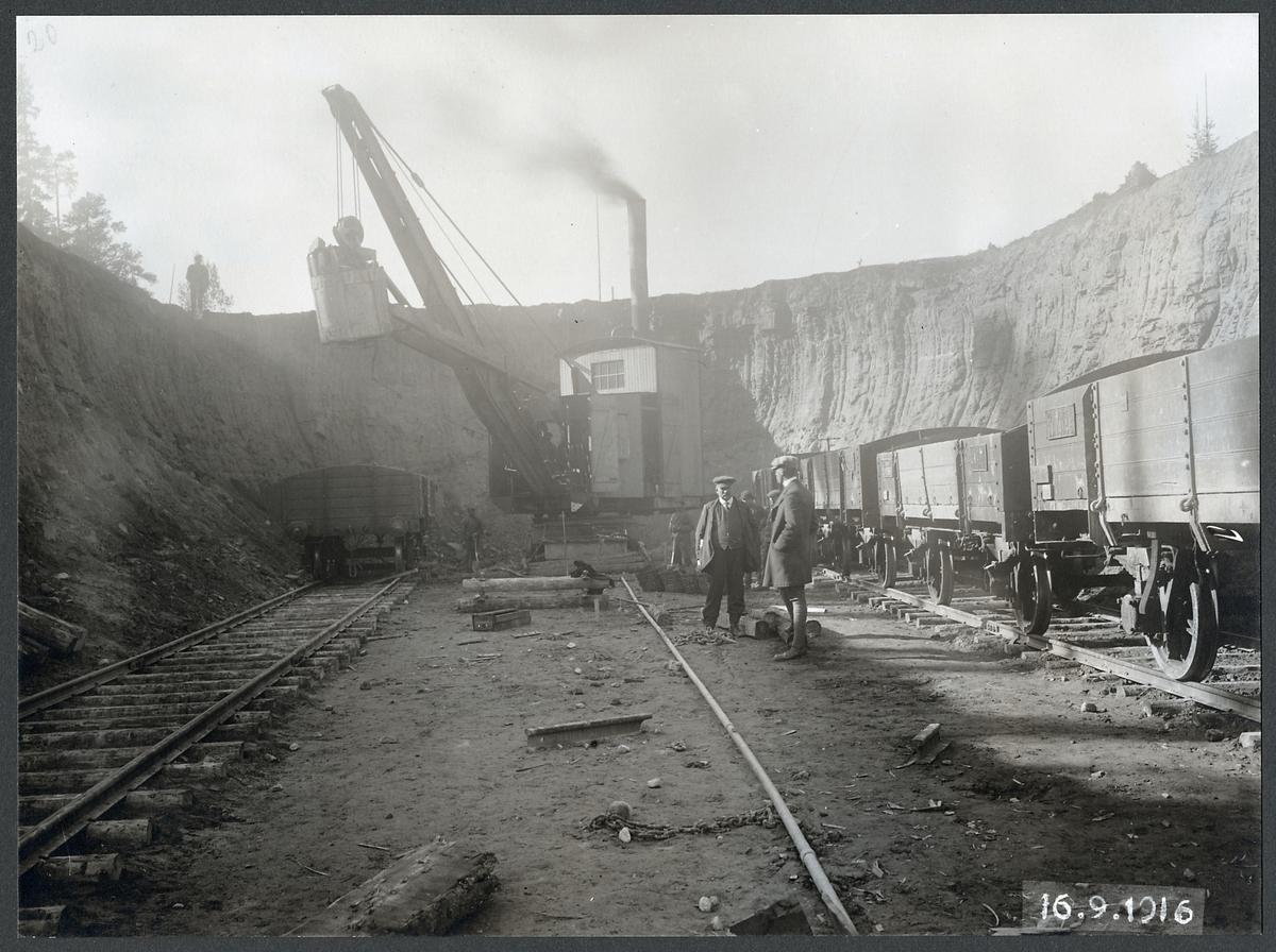 Grävmaskinsarbete under byggnaden av Tallbergsbron. Statens Järnvägar, SJ godsvagn 14145.