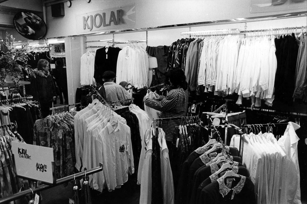 Tre damer tittar på blusar, skjortor och annat på damavdelningen på Lindex, Kungsgatan 32, kvarter Pärlan 7. I november 1990 flyttade butiken tillsammans med Gulins (senare Adelsten) in i Epas gamla varuhus i kvarter Storken 12.