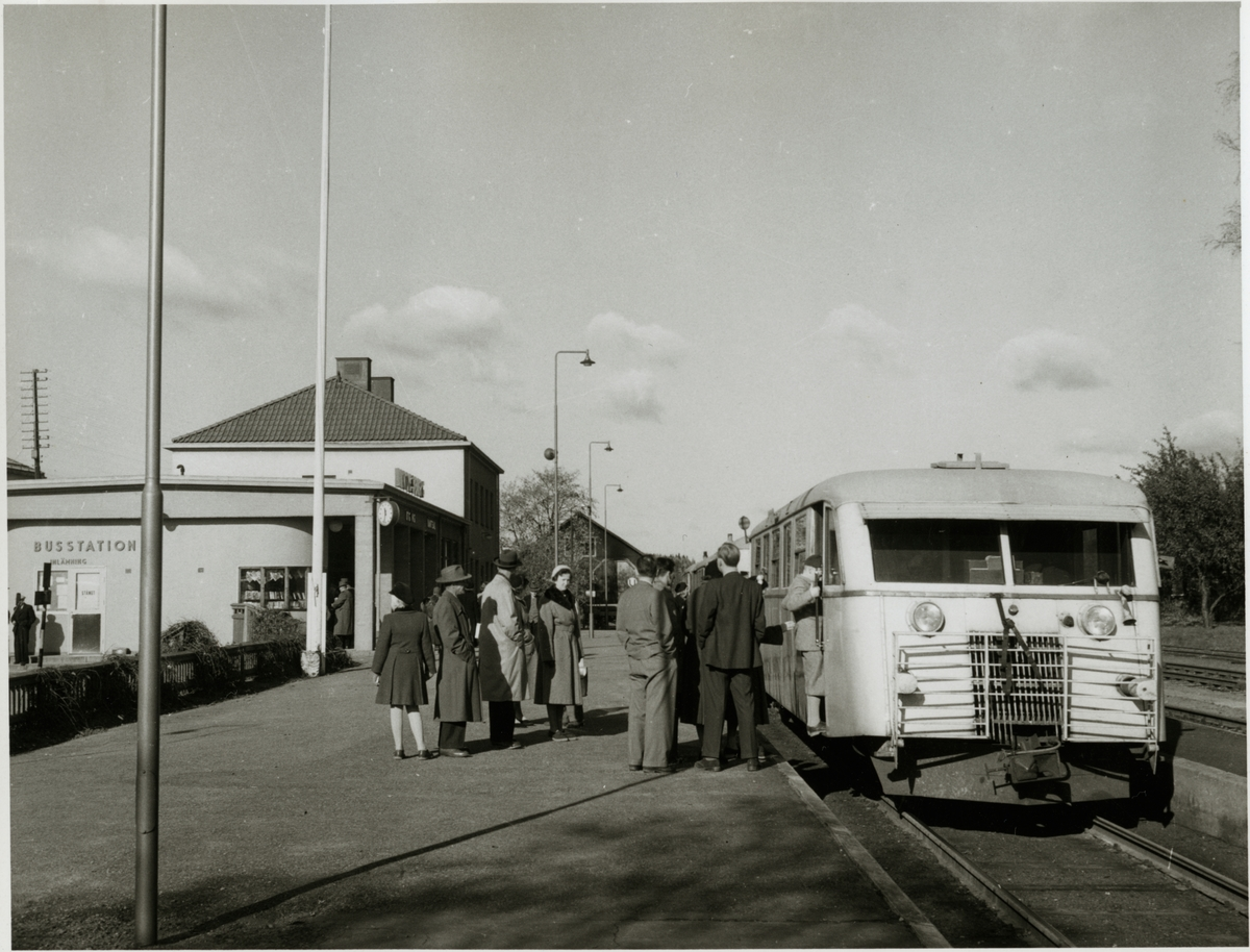 Lindesberg järnvägsstation med resande och rälsbuss vid perrong.
