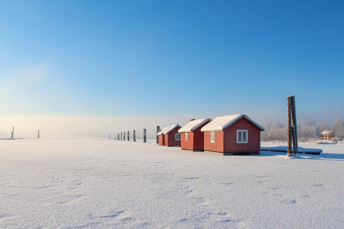 Foto av røde flytende hus på rekke på snødekket elv i fint vintervær. (Foto/Photo)
