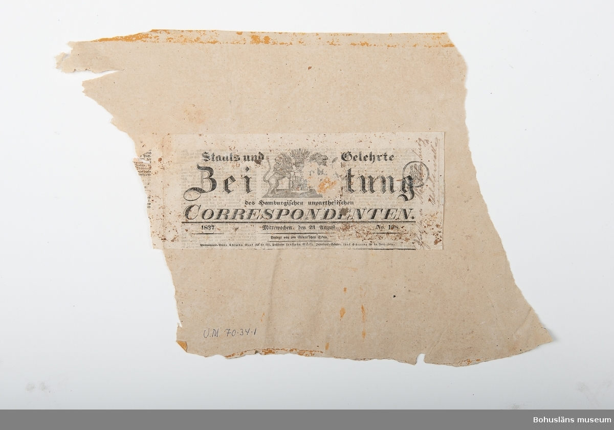 """Fragment som visar två lager blommönstrade tapeter. Överst en rosa-gul-grågrön tapet, under en med ljust gulröda blommor mot gul botten. På baksidan klistrad del av tyskt tidning """"Zeitung Correspondenten"""" från den 23 augusti 1837 med handskriven anteckning """"..... Mecklenburg Uddewalla"""". Tapetfragmentet är från Snäckan, Gustafsberg, Uddevalla."""