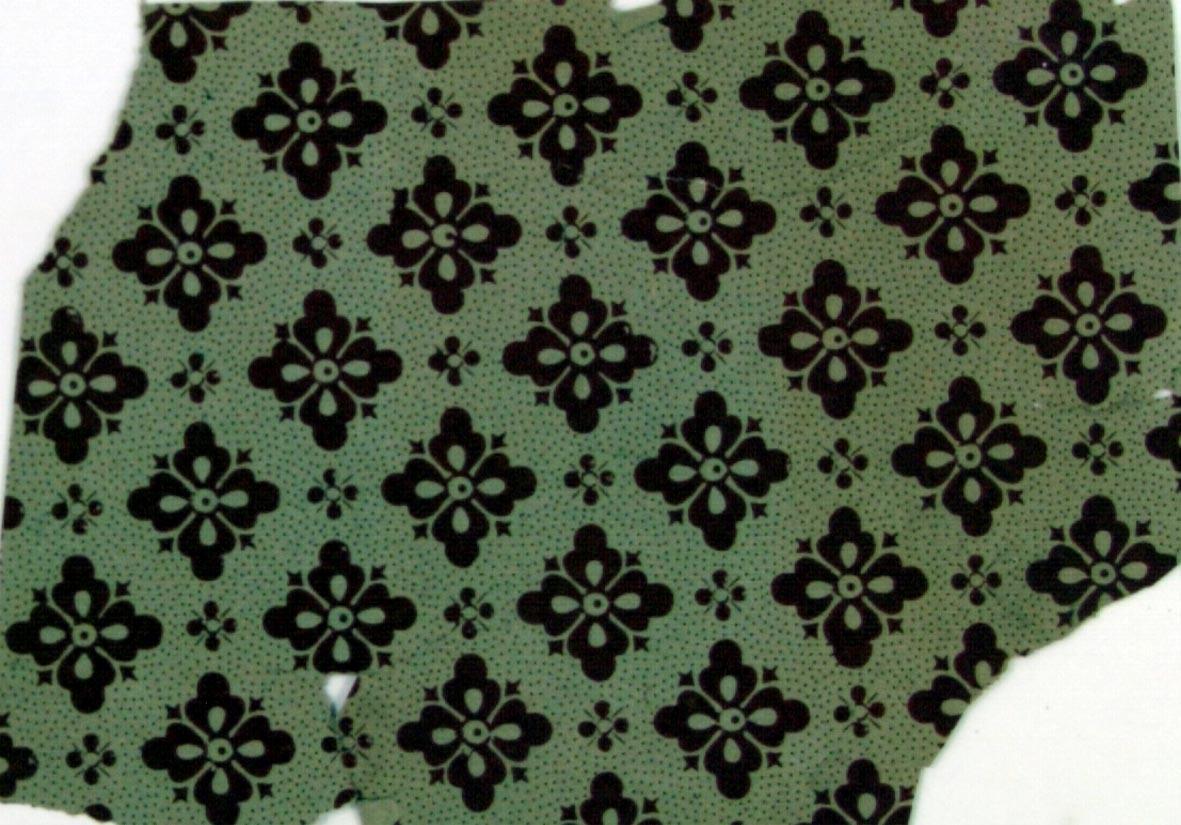 Fyrklöver i diagonalupprepning på ett ljusbrunt genomfärgat papper dekorerat med ett litet prickmönster. Tryck i chokladbrunt.
