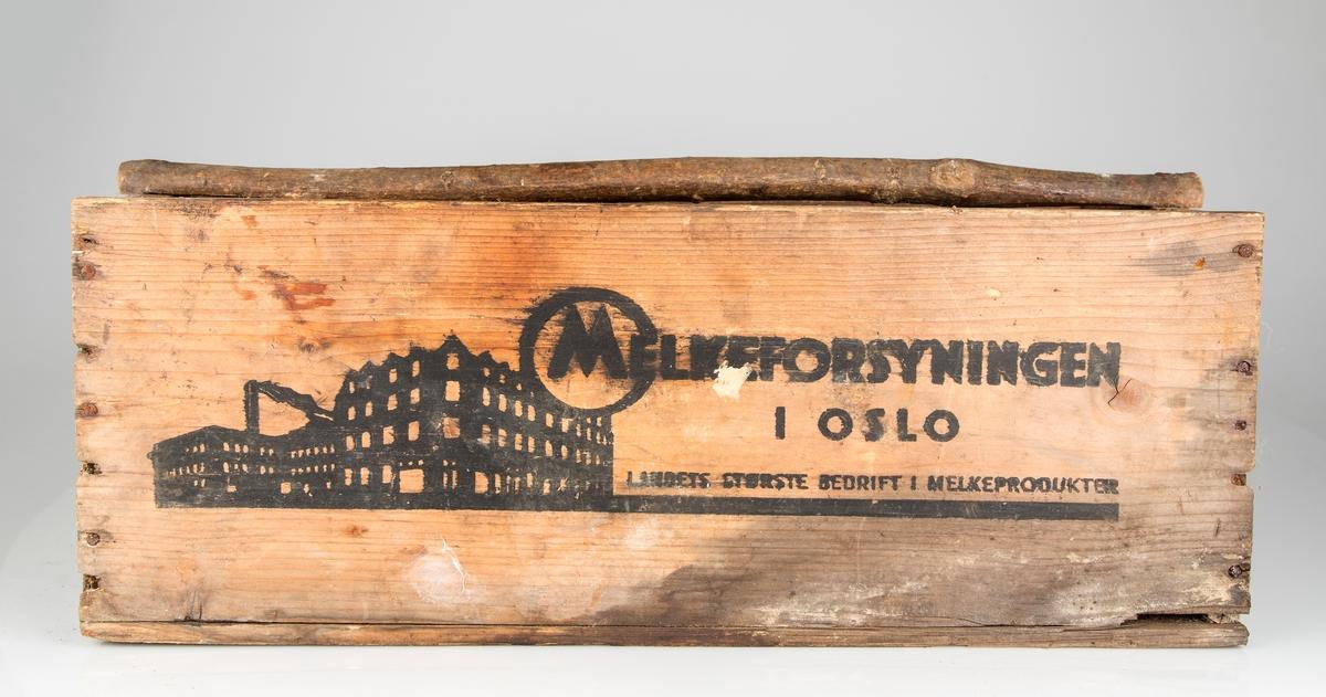 Trekasse fra Meieriforsyningen til transport og oppbevaring av smørpakker. Uoriginalt, enkelt håndtak av trepinne med bark.
