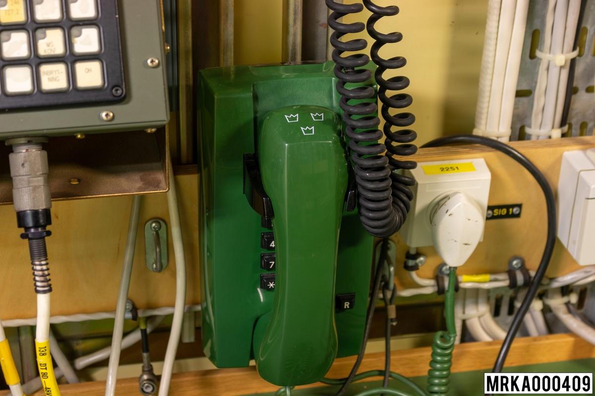 Telefonapparat utrustad med tonknappsats för DTMF-signalering (Dual Tone Multi Frequency) och s k registerknapp. Denna har samma funktion som nollan på en telefonapparat med fingerskiva (utom vid nummertagning).  Väggtelefon med kåpa och mikrotelefon i grön plast, knappsats med tio knappar för impulsval, väggfäste, ringklocka reglerbar i tre steg, elektretmikrofon och elektronisk talkrets med automatisk dämpningskompensering. Det finns fyra telefoner med tonvalsknapp i sambandcentralen (SBC).