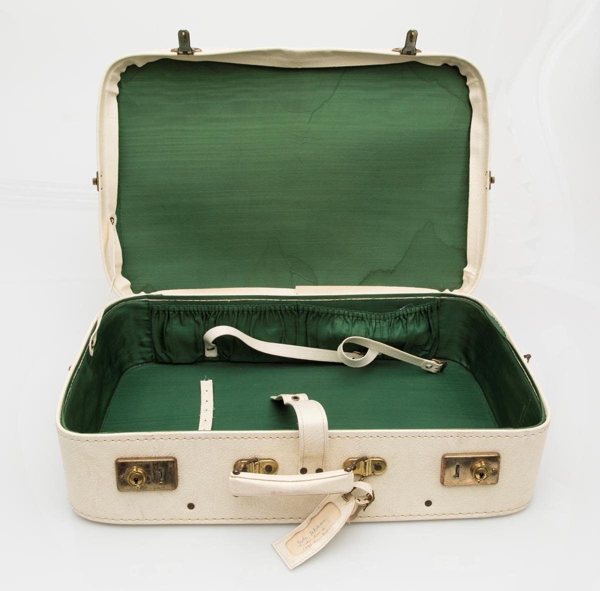 Hvit koffert med rem over lokket. To låser foran og to hekter på sidene. Fôret med grønt stoff. Adressemerkelapp.