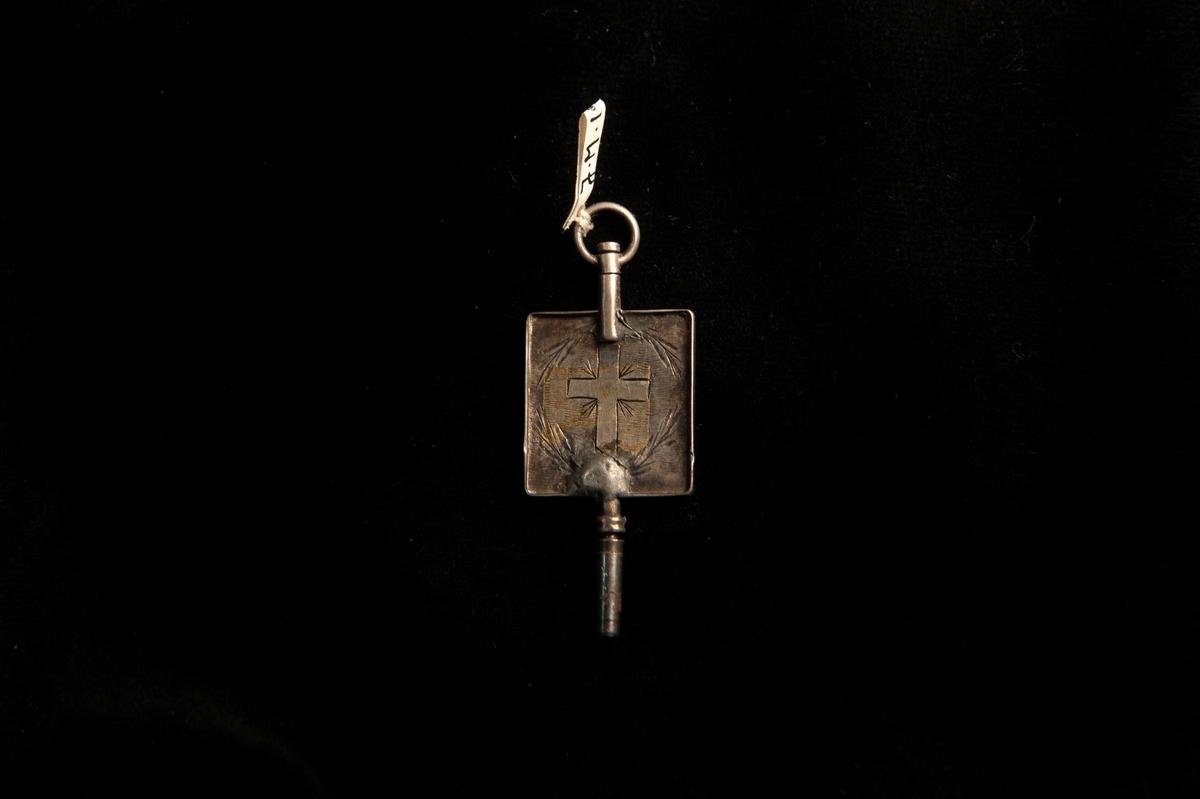 En urnyckel av silver, med fyrkantigt handtag. På ena sidan ett graverat kors och på det andra ett hjärta. Inom hjärtat stämplar.