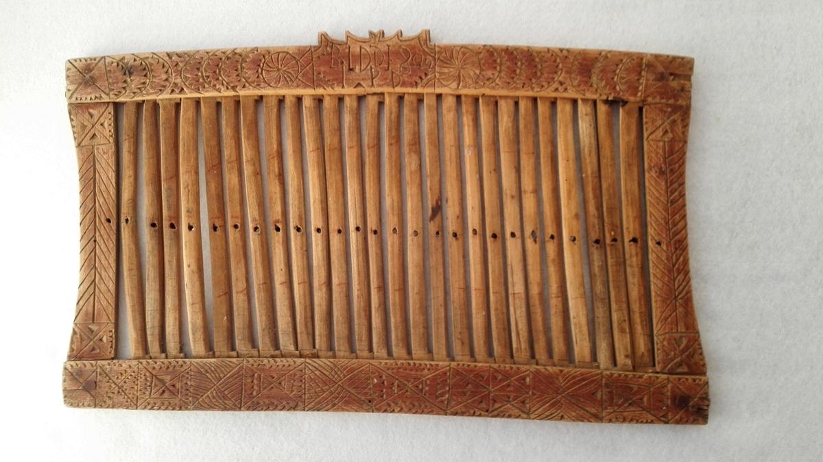 Form: Firekanta Bandgrindvæv.  Firkantet baandgrind 33 x 19,5 cm med 26 ca. 14 cm lange spiler. Rammen er paa begge sider rødmalt og forsirt med karveskurd. Paa den ene siden indskaaret: A.O.S.D. og paa den anden BLDD 1800/ J.P.D. Kjøpt fra Mari Hove, Vik.