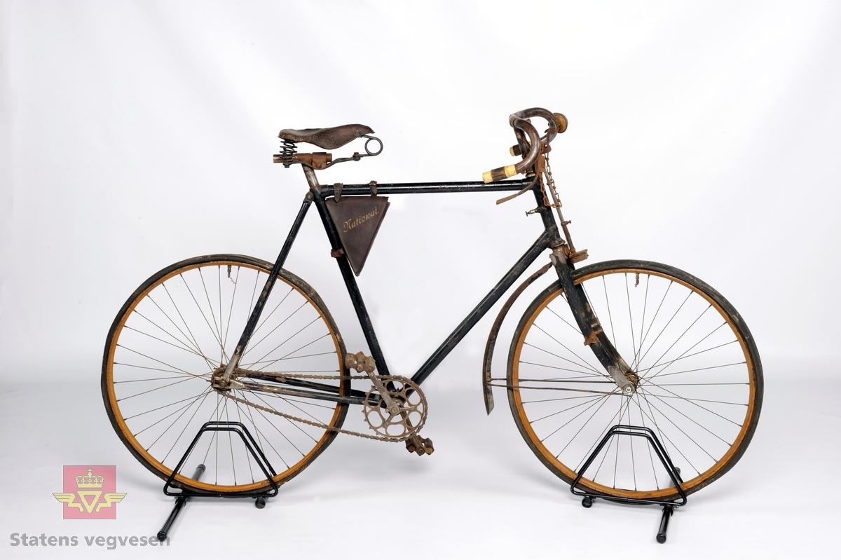 Sykkel, landevegsracer. Dekk: originaldekkene sitter fortsatt på men typen er uleselig. Nav foran: Eget fabrikat, Norsk Bicyclefabrik. Bak: Fastnav av eget fabrikat. Bremser: klossbrems rett på fordekket. Hovedfarge er svart.