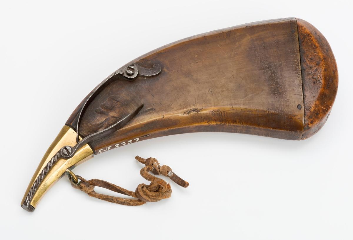 Hornet har tykk, avrundet bjørkebunn. I spissen på hornet er det en messingholk som har lukkeanordning med fjærsystem, dekorert med skråstreker fremst ved spissen.  Ring med lærrem i satt på messingholken.