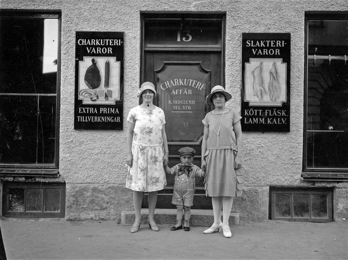 Elin, Greta och Erik Skoglund står utanför familjens charkuteriaffär på Nygatan 13 i kvarteret Storken, Alingsås.