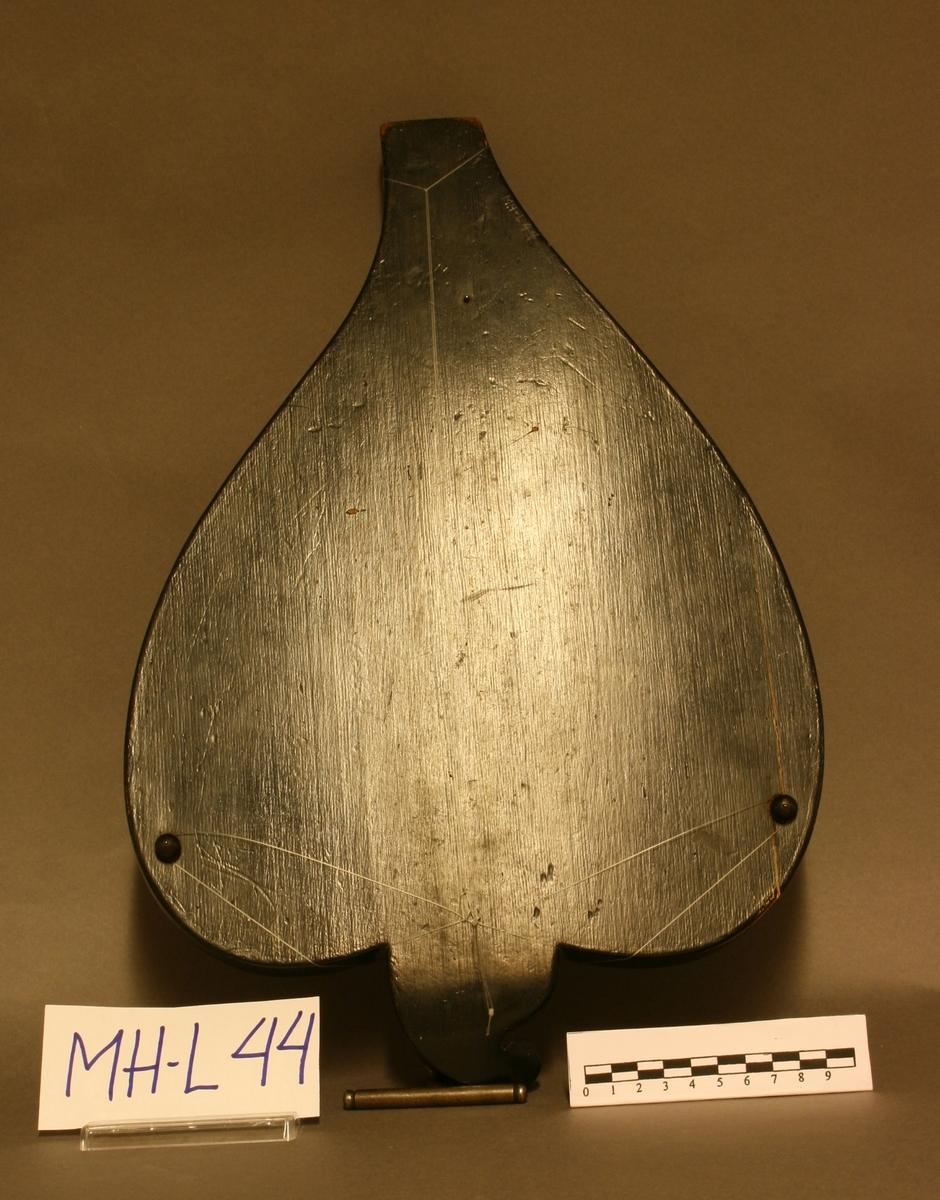 Hjerteformet korpus med sortmalt bunn og sarg. To runde lydhull i lokket. Gripebrett løper på tvers, 4 stemmeskruer av metall på tilnærmet snekkeformet skrueplate. 4 anhengstifter i anhengsplate ved spissen av korpus. 26 metallbånd på gripebrettet, perlemorsøyne mellom 4.-5., 8.-9., 11.-12. bånd. Kassen står på tre kuleben. To trykte etiketter på bunnen innvendig: GEORG TIEFFENBRUNNER//MÜNCHEN//Petersplatz No. 8/1. Total lengde: 40,7. Største bredde: 27,2. Høyde sarg: 2,3. Med tilhørende stemmenøkkel. Trygve Lindemans liste nr. 235