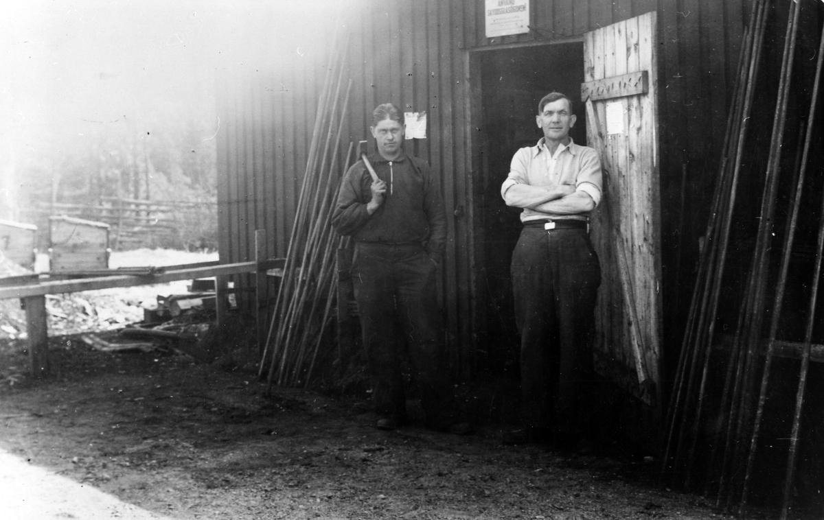 Två stycken arbetare från Statens Arbetlöshetskommision står framför ett träskjul i Fryele, Småland. Till höger står Folke Augustsson, metallarbetare från Alingsås.