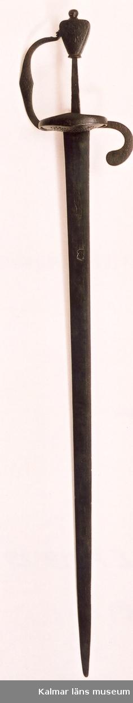 KLM 6589 Värja, av järn. Rak tveeggad klinga med linsformig genomskärning. På båda sidor återfinns Johannes Wundes (Solingen 1560-1610) stämpel (ett krönt huvud), på terssidan dessutom ulvmärke och ett riksäpple med dubbelt kors och SS. Fäste av järn med punsad ornering (serafhuvud, blad och blommor). Genombruten parerplåt, bakre parerstång, handbygel och tumring i ett stycke. Flat päronformig knapp, ornerad. Datering, från 30-åriga krigets tid.