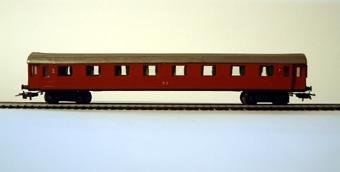Modell av personvagn B05b i skala 1:87. Vagnen är gjuten i brunfärgad plast, och har Märklin-boggi.  Modell/Fabrikat/typ: Ho