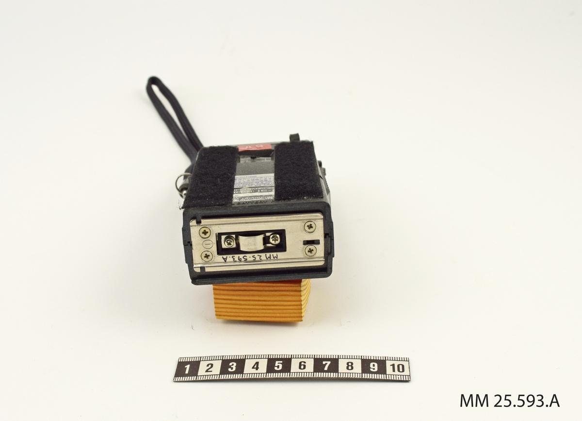 Svart rektangulär radio med plasthölje. På ovansidan sitter två vridreglage märkta VOL och SQL. Bredvid en anbslutningskontakt för antennen. Under reglagen sitter en kanalväljare bestående av en knapp som kan skjutas mellan lägena K1 och K2 samt tre svarta, räfflade hjul som kan vridas till önskat läge. Det första hjulet har bokstavsbeteckning, de resterande två siffror.   På radions framsida finns överst ett räfflat område med högtalar och mikrofon. Därunder ett svart område på vilket tre dymo-lappar har klistrats. Högst upp i hörnet finns tillverkarens logotype och modellbeteckningen.   På baksidan finns en knapp som kan skjutas mellan lägena LOW och HIGH för att ställa in önskad RF POWER. Därunder tillverkarens skyltar. Över baksidan har två kardborreremsor klistrats fast.  Undersidan av blank metall med anslutning för batteriet. På radions högra sida finns en SM-omkopplare, på den vänstra ett snöre i en metallring.